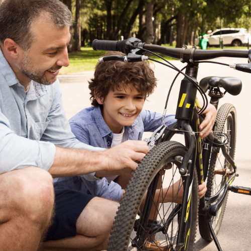 Dad Fixing Bike with Son